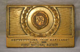 Bronze-colored rectangular medallion marked First National Agency