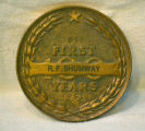 Bronze-colored medallion commemorating First 100 Years