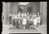 27 elementary school students in front of brick school