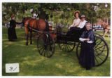 An unidentified woman and Trip DeMann in a horse-drawn cart, with Aleta Bow standing beside at...