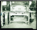 A machine for shearing corrugated steel inside the Northfield Iron Company workshop