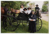 Audrey, Gus, and Trip DeMann in a horse-drawn cart, with Aleta Bow standing next to them and Chip...